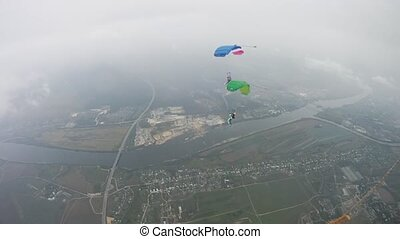 Parachutists flying in sky over green field. Extreme active...
