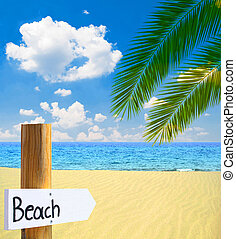 Paradise beach and sea with wooden board showing direction to the beach