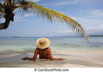 Paradise Island - Woman sunbathing under a coconut palm leaf...