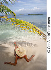 Paradise Island - Woman sunbathing under an overhanging...