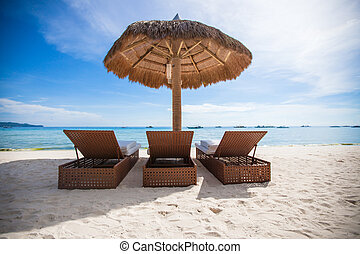 Paradise view of nice tropical empty sandy plage with umbrella and beach chair