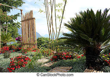 Paradisiac garden with bamboo, palm tree and red flowers in front of mountains