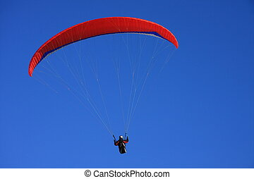 Paraglider against blue sky - Single paraglider with red...