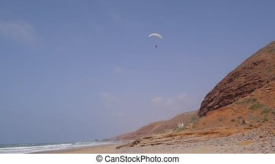 paraglider fly above beach