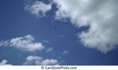 Paraglider flying in the sky at sunny day