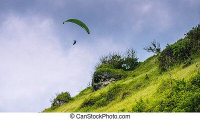 Paraglider flying off the Grassy Hills above Gunung Payung Beach, Bali.
