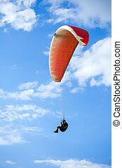 Paraglider flying on blue sky