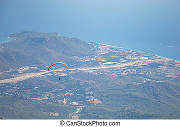 Paraglider flying over mount Tahtali, Turkey, Kemer. Paragliding in the mountains