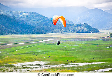 Paraglider flying over the beautiful Pokhara valey, Nepal.
