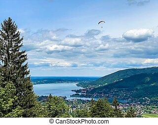 Paraglider flying over the lake. Paragliding under Bavarien landscape