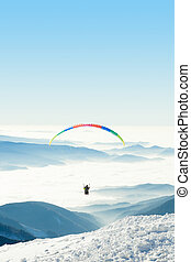 Paraglider in the sky above a snowy mountain top