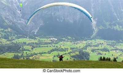 Paraglider takes off from Mount First and flies over the Lauterbrunnen Valley in Switzerland.
