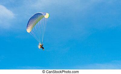 Paraglider on blue bright sky