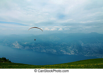 Paraglider over lake and mountains