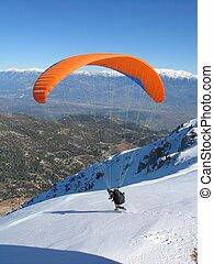 Paraglider snow launch - Paraglider with an orange wind...