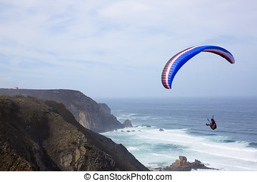 paragliding above the ocean at Castelejo beach in Portugal
