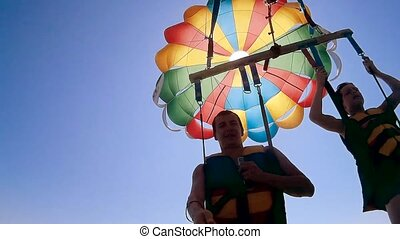 paragliding and parasailing lifestyle. ocean man and boy are...