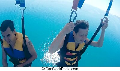 paragliding and parasailing lifestyle. man and a boy are...