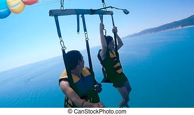 paragliding and parasailing lifestyle. man and boy are flying on a ocean parachute over the sea. Extreme sport first-person view