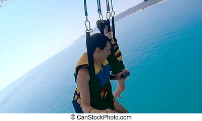paragliding and parasailing lifestyle. man and boy are...