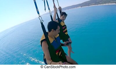 paragliding and parasailing lifestyle. man and boy are flying on a parachute over ocean the sea. Extreme sport first-person view