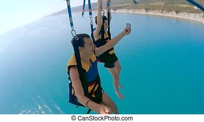 paragliding and parasailing lifestyle. man and boy are ocean...