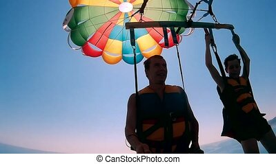 paragliding and parasailing lifestyle. man and boy ocean are...
