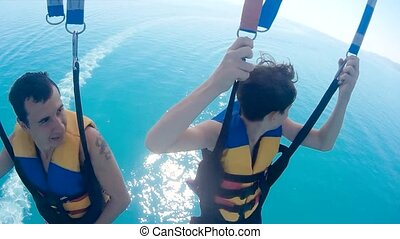 paragliding and parasailing. man and a boy are flying on a...