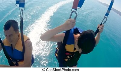 paragliding and parasailing.man and a boy are flying on a...