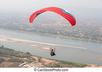 Paragliding in the sky. Paraglider  flying over Landscape from Beautiful View Mekong River
