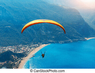 Paragliding in the sky. Paraglider tandem flying over the sea