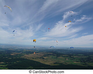 Many paragliders in Auvergne in France over the Puy de Dome