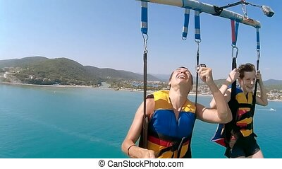 paragliding ocean and parasailing lifestyle. man and boy are...