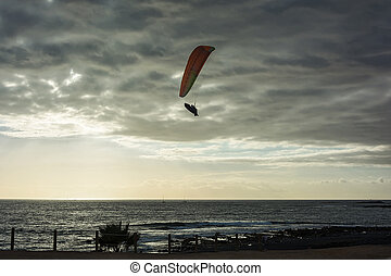 Paragliding on the background of a marine landscape at sunset
