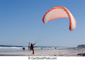 Paragliding - Paraglider prepares for takeoff on the beach