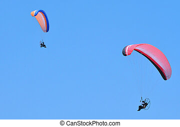 Paragliding - Two paragliders are paragliding against clear...
