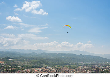 paragliding under blue sky in the town