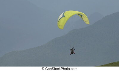 Paragliding with two people over mountains in slow motion