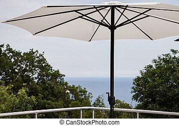 paraguas playa, con, mar, en, plano de fondo