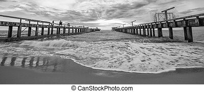Parallel concrete piers on beach and sea wave