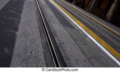 Parallel tram line rails on wide new asphalt road in buildings shadow in historical district under bright sunlight in spring