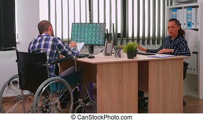 Paralysed financial expert sitting in wheelchair analysing economy statistics of company in business office discussing with woman manager. Handicapped, immobilized businessman using modern technology.