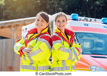 Paramedic and emergency doctor in front of ambulance