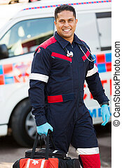 paramedic carrying portable equipment - handsome young...