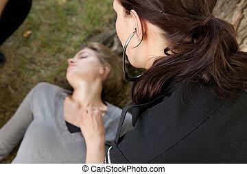 Paramedic Checking Vitals - Paramedic checking vitals on an...