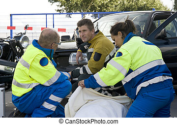 protect - paramedic covers a patient with a blanket to ...