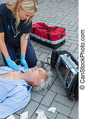 Paramedic examining unconscious elderly patient lying on street