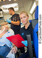Paramedic helping injured patient in ambulance