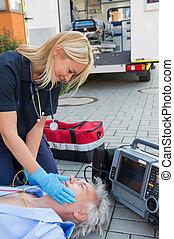 Paramedic helping injured patient on street