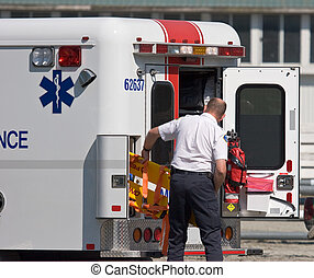 Paramedic - paramedic unloading back board from stretcher at...